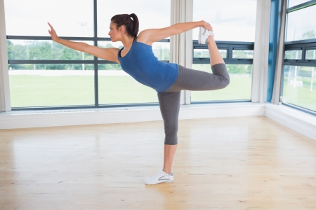 Woman doing yoga pose in fitness studio photo