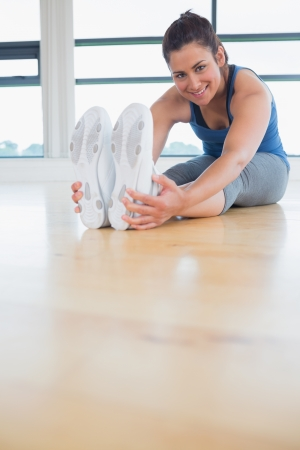 Happy woman stretching legs in fitness studio photo