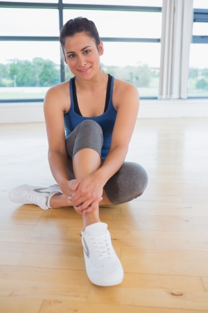 Happy woman sitting in fitness studio of gym photo