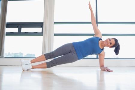 Happy woman in yoga pose in fitness studio photo
