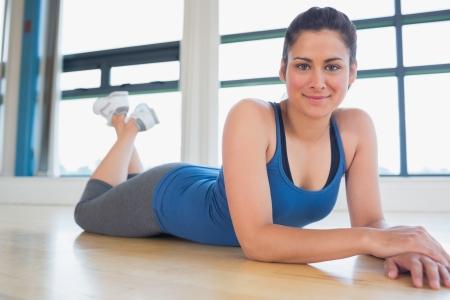 Woman lying on floor of fitness studio photo