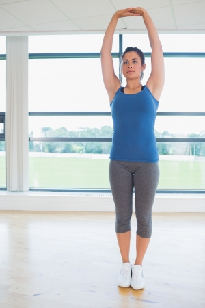 Woman standing in yoga pose in fitness studio photo