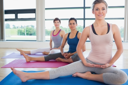 Woman in yoga class stretching on floor photo