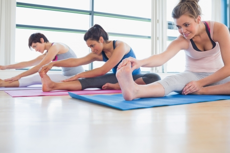 yoga class: Women stretching in yoga class in fitness studio Stock Photo