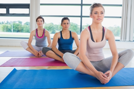 Women sitting in bound angle yoga pose in fitness studio photo