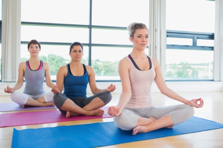 Women meditating in easy yoga pose in fitness studio photo