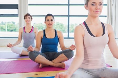 Women sitting in easy yoga pose in fitness studio photo