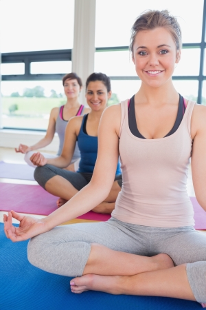 Happy women sitting in easy yoga pose in fitness studio photo