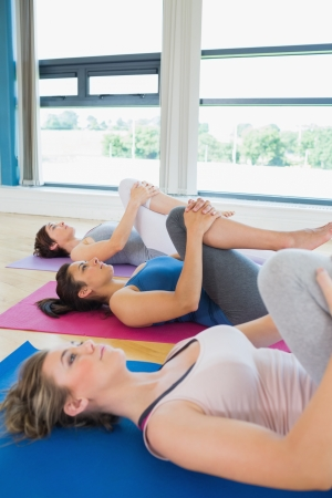 Women in fitness studio stretching legs in the gym photo
