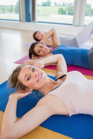 Women on mats doing sit ups in fitness studio Stock Photo - 15591536