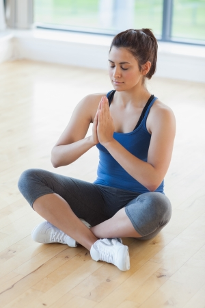 spare time: Woman sitting on the floor in yoga pose in fitness studio Stock Photo