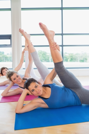 Women on mats stretching legs in fitness studio photo