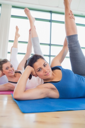 Women stretching legs in fitness studio photo
