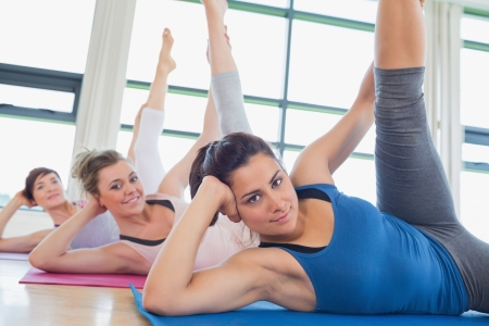 Happy women stretching legs in fitness studio photo