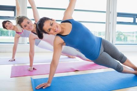 L�chelnde Frauen in Yoga-Klasse im Fitness-Studio Stockfoto