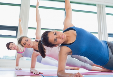 health clubs: Women in side plank yoga pose in fitness studio