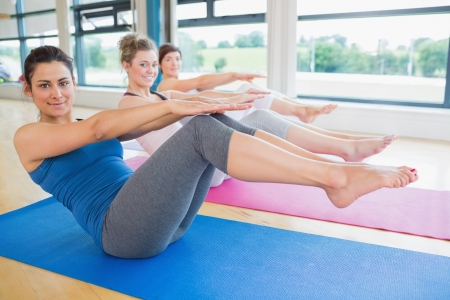 Happy women doing boat pose in yoga class in fitness studio photo