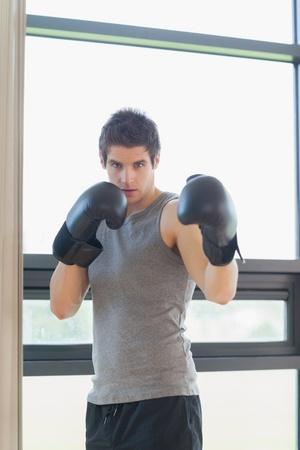 hit man: Man standing at the gym while boxing