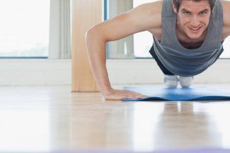 push ups: Man doing push ups at the gym while smiling