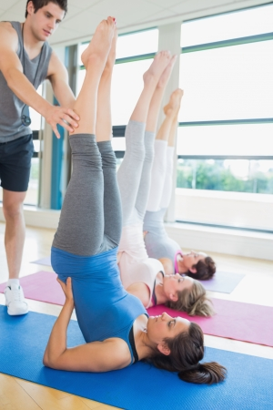 Trainer helping woman at yoga class in fitness studio photo