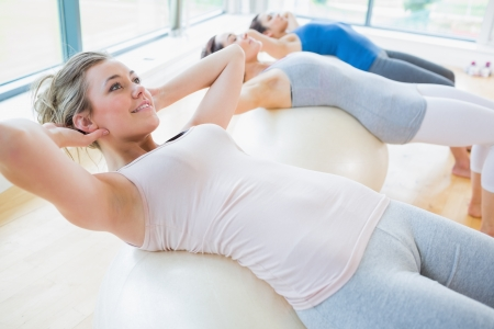 physio: Women doing sit ups with exercise ball Stock Photo