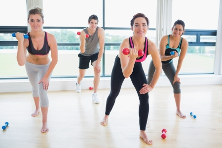 Smiling people lifting wights in aerobics class in fitness studio photo