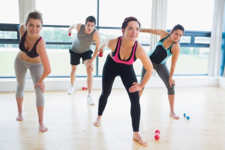 People in aerobics class lifting weights in fitness studio photo