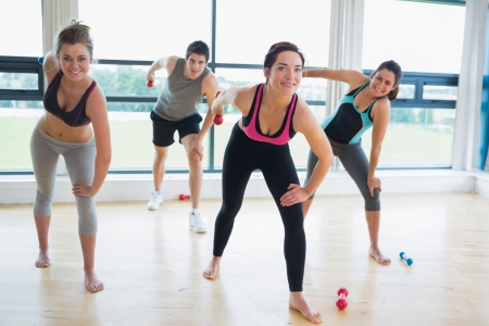 Happy people in aerobics class in fitness studio photo