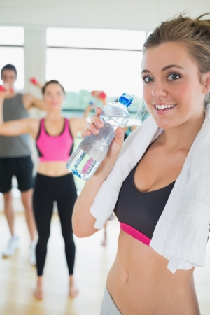 Woman with water and towel in aerobics class photo