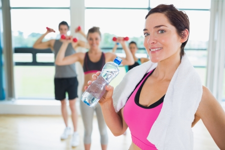 Woman taking break from aerobics class in fitness studio photo