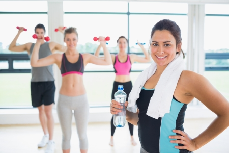 Woman at front of aerobics class in fitness studio photo