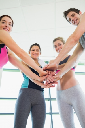sports hall: People putting hands together at the gym smiling