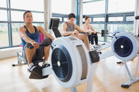 exercise machine: People working out on row machines in fitness studio