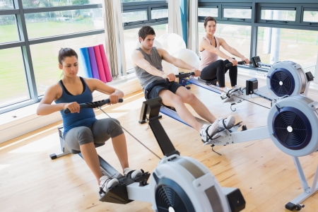 Three people on rowing machines in fitness studio photo