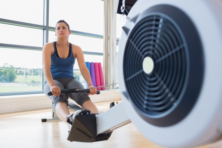 Woman taking break from rowing mahcine in fitness studio photo