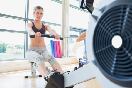 Woman exercising on row machine in fitness studio photo