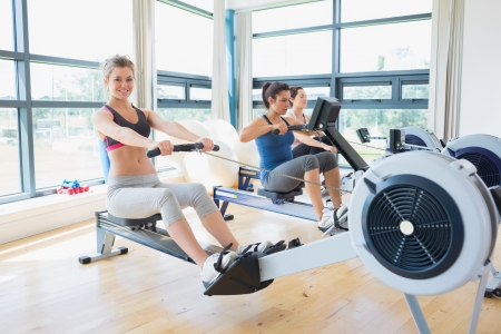 Woman sitting at the row machine at the gym smiling  photo