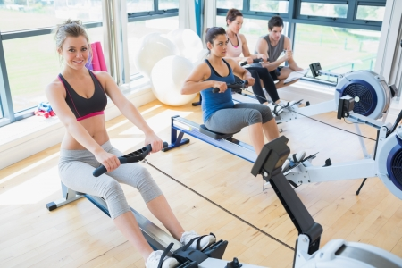 rowing: People sitting at the row machine at the gym