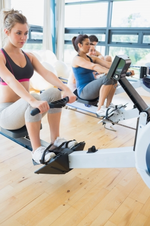 Man and womenusing the row machines in fitness studio photo