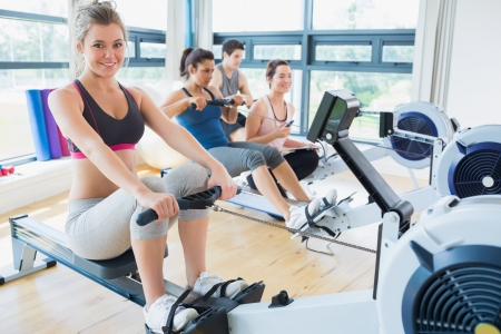 man machine: Smiling woman on rowing machine with others in fitness studio Stock Photo