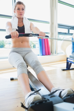 Woman on the rowing machine in fitness studio photo