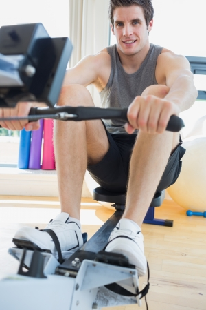 rowing: Man working out on row machine in fitness studio Stock Photo