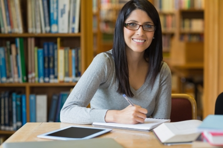research study: Smiling woman taking notes while doing research in a library Stock Photo