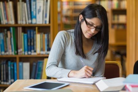 sachant lire et �crire: Femme aux cheveux noirs �tudier dans la biblioth�que