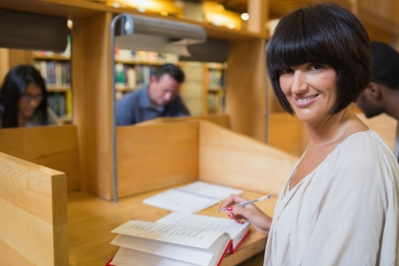 Black-haired woman reading a book in library at desk photo