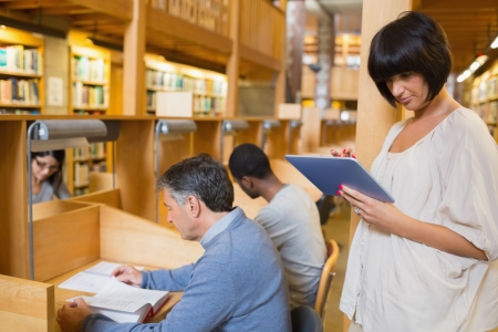 Woman holding tablet pc while other persons reading in the library Stock Photo - 15593421
