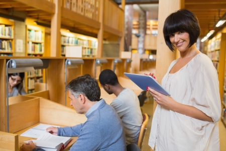 Smiling woman holding a tablet pc while other persons reading in the library Stock Photo - 15593486
