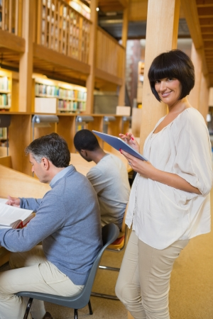 Smiling woman holding a tablet pc in library Stock Photo - 15585036