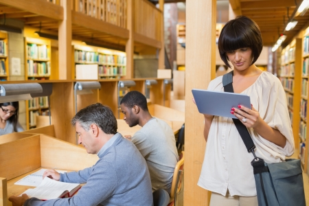 Woman looking at her tablet pc while other people are reading in the library photo