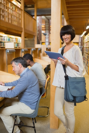 Woman with tablet pc in library while people are reading photo